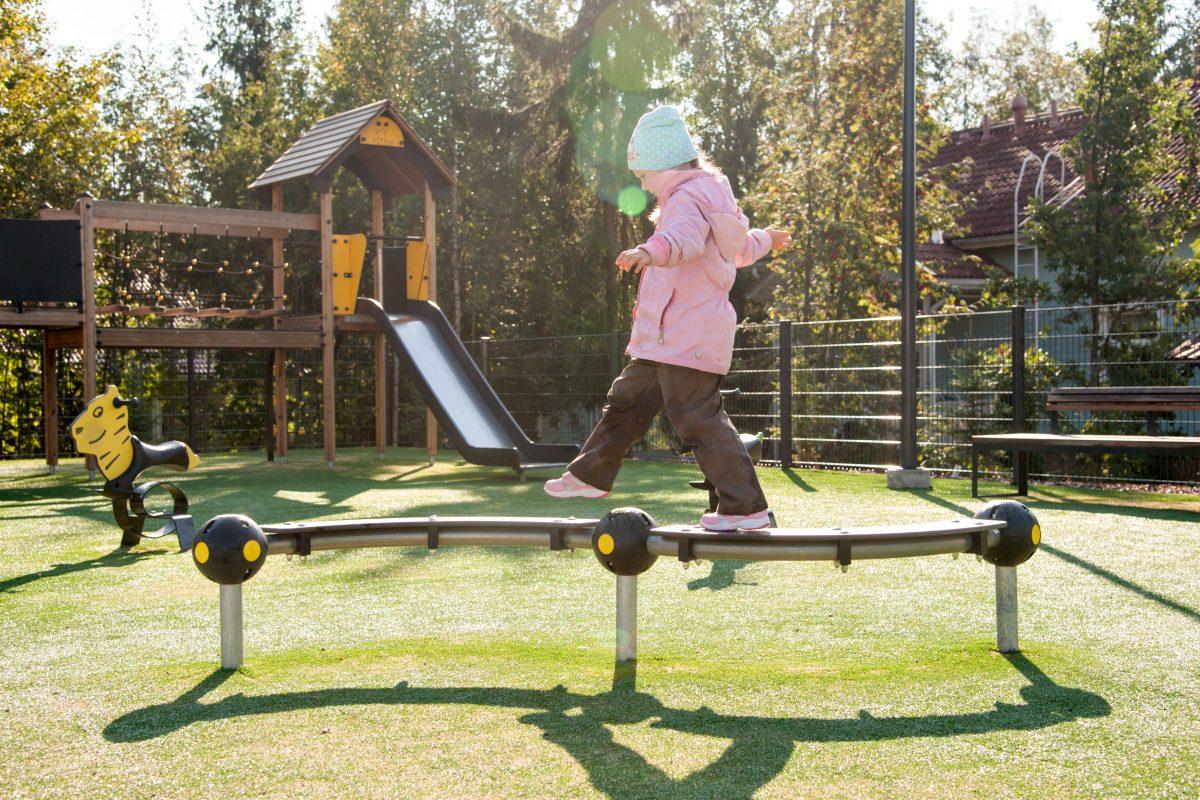 Kuvassa lapsi kävelee leikkupuistossa puomin päällä.